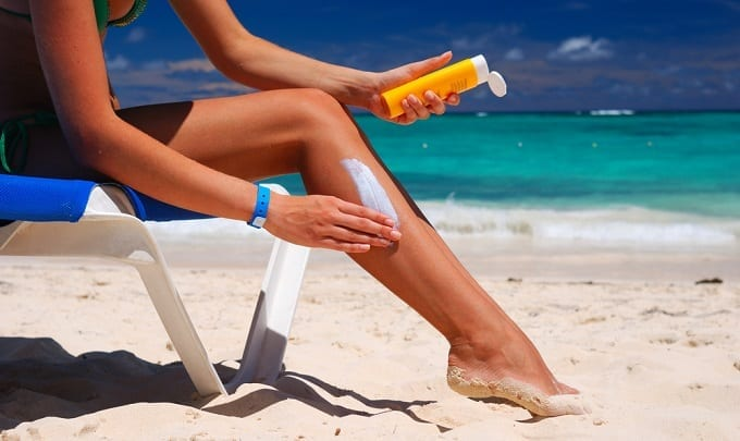Woman Applying Sunscreen On The Leg