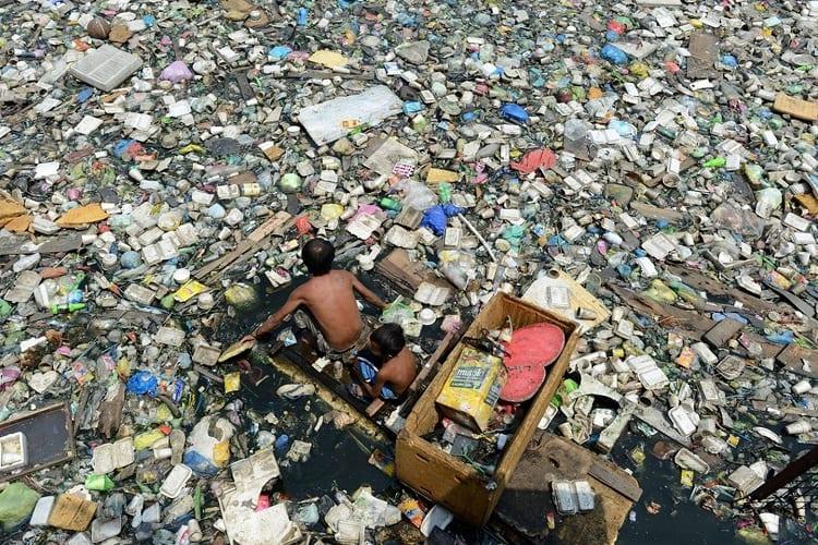 Man In Boat Floating Through Ocean Garbage